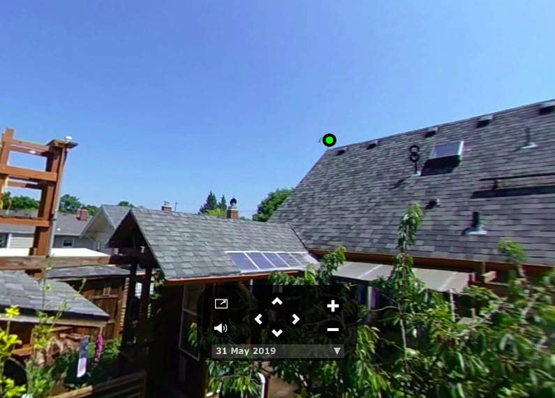 This is part of the interactive panorama for May 31, 2019. The green dot near the roof of the main house marks the weather station (see figure 3 for the data block that pops up when you click on the dot) and the black box in the lower middle of the frame is the scene control panel (see figure 2).