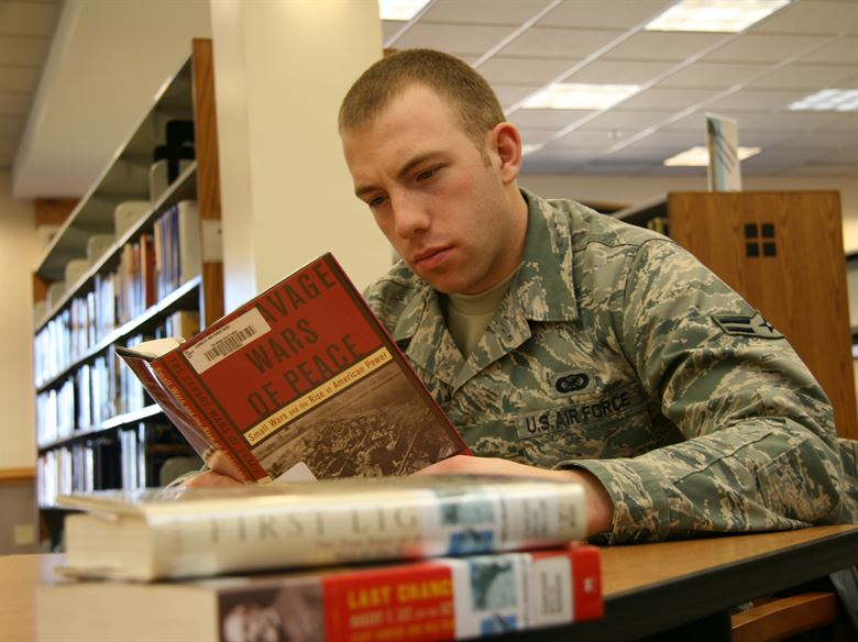 Photograph: a uniformed military person reading in a library