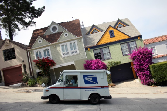 Photograph: A mail truck parked on a hill, with the photo frame oriented parallel to the crooked ground