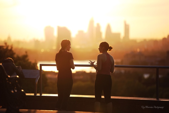 Photograph: Two people talking in front of a sunset
