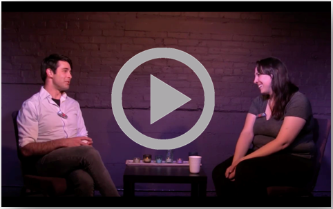 Screenshot from Storytelling with Robyn Vazquez. Two people seated across from each other smiling and talking.