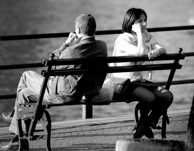 Photograph: Two people sitting on a park bench, facing away from each other in silent anger