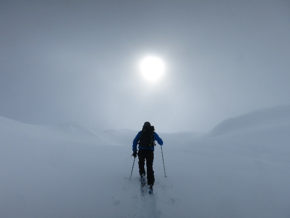 Photograph: A person cross-country skiing up a hill toward the sun.