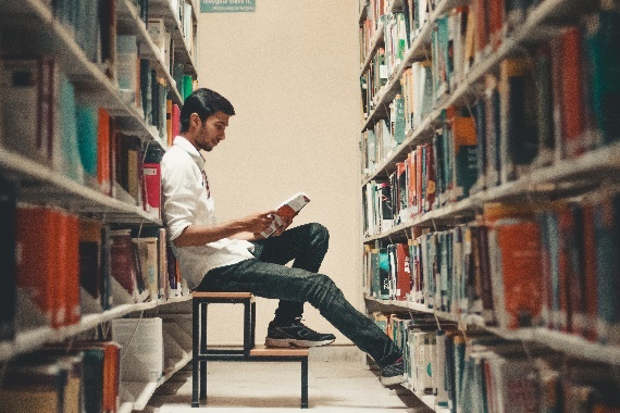 Photograph: person reading and sitting on a stool between shelves of books.