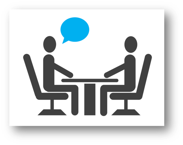 Image: Two people sitting across from each other at a table, one speaking to the other.