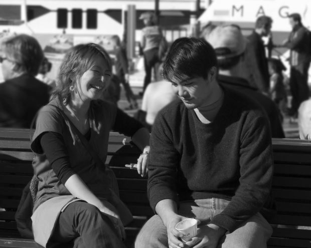 Photograph: Couple sitting; man looking down while woman is smiling