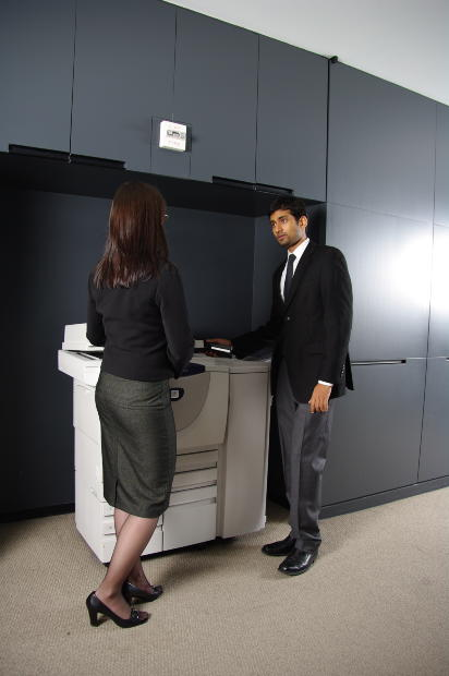 Photograph: Two office workers talking at printer-copier machine